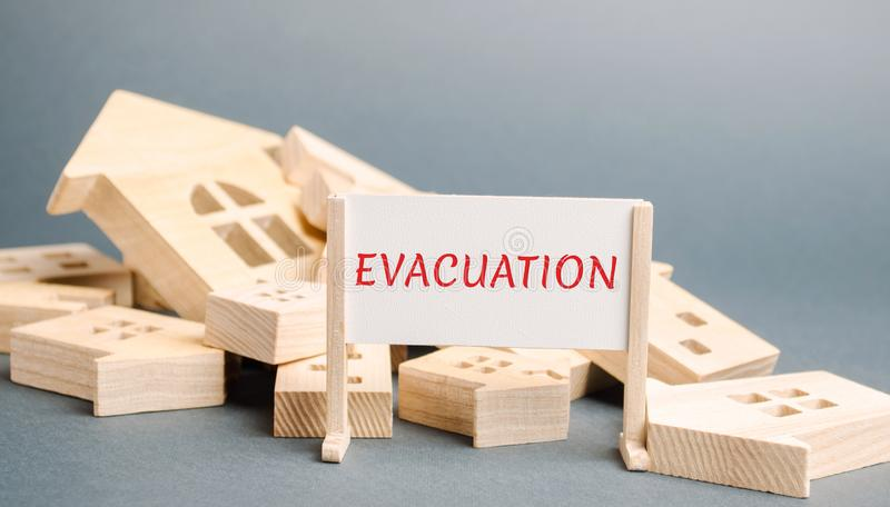 A poster with the words Evacuation and fallen wooden houses. Removal of people, institutions, property from hazardous areas. royalty free stock image