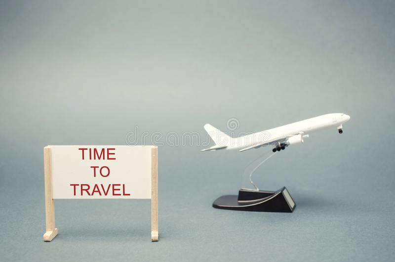 A poster with the words Time to travel and a miniature airplane. The concept of planning a summer or winter vacation. Family rest. Hot tours. Available offers stock photography