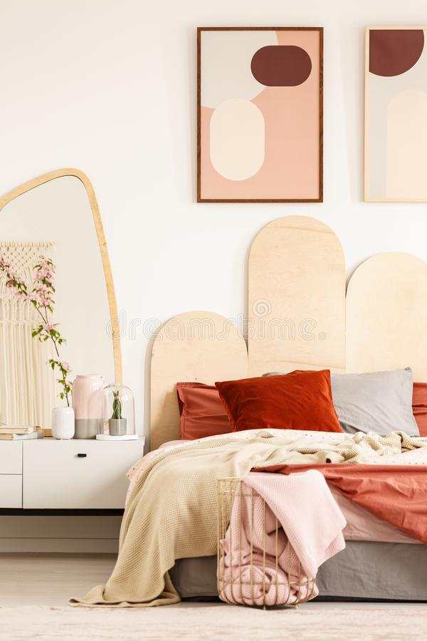Posters above bed with red pillows in modern pastel bedroom inte stock photo