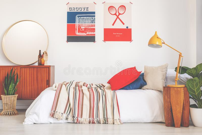 Posters above bed with striped blanket in bedroom interior with plant and yellow lamp. Real photo royalty free stock photos