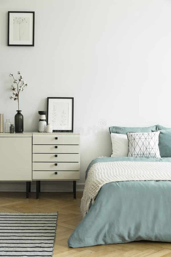 Posters and cabinet with plant in white bedroom interior with bl. Anket on green bed. Real photo royalty free stock photo