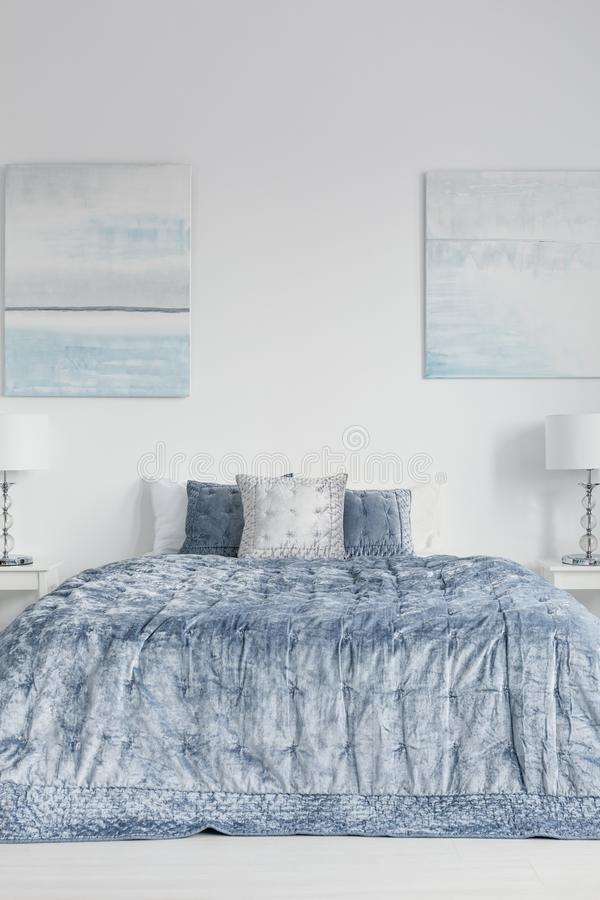 Posters on white wall above bed with blue sheets and cushions in bedroom interior with lamps. Real photo stock photography