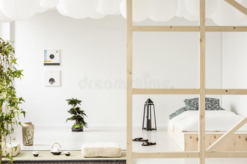 Posters on white wall above bonsai in bedroom interior with lantern stock photos