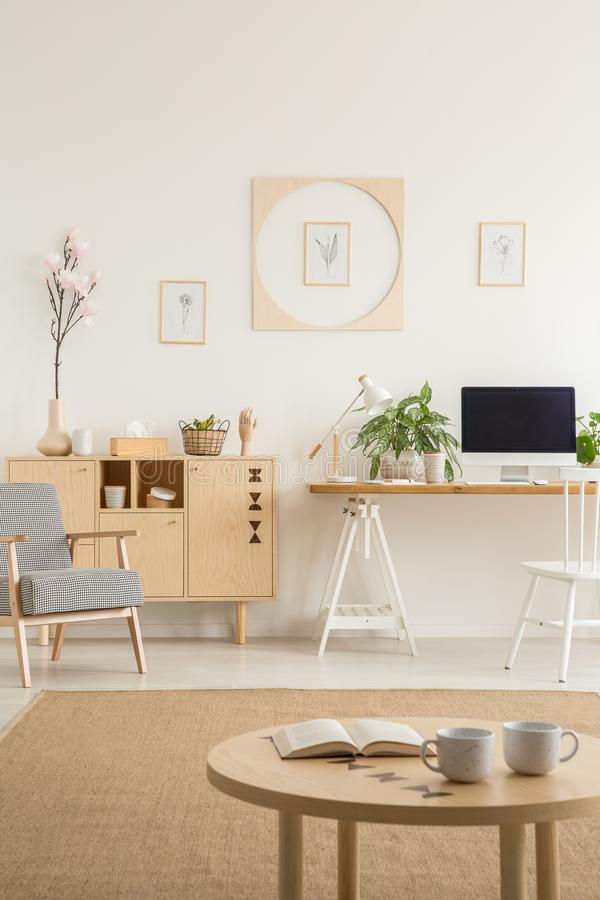 Posters on white wall above desk with desktop computer next to c. Abinet in flat interior. Real photo concept royalty free stock photography