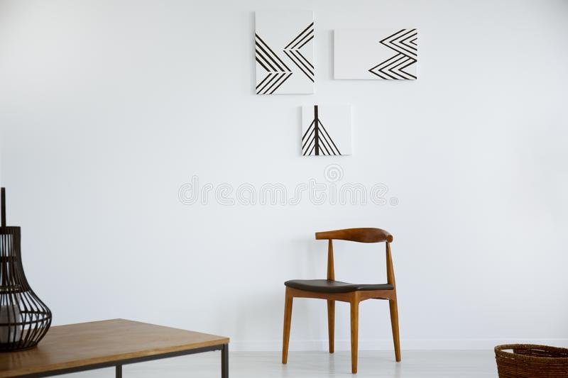 Posters on white wall above wooden chair in minimal living room interior with table. Real photo stock image