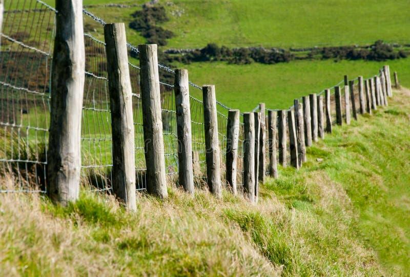 Postes de Wodden con la cerca de alambre de metal en campo del ganado fotografía de archivo