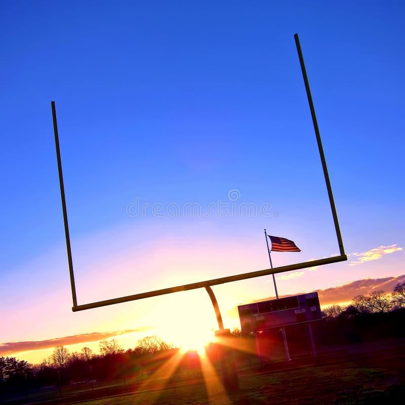 Postes do futebol americano e bandeira dos E.U. no por do sol imagens de stock
