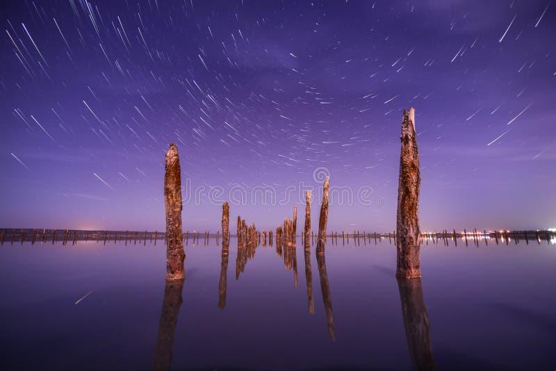 Postes en el agua en la noche con la estrella se arrastran imágenes de archivo libres de regalías