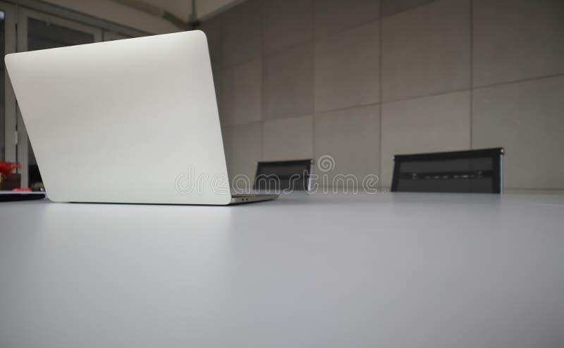 Posti d'argento del computer portatile sulla tavola bianca dell'ufficio con il telefono cellulare, le matite ed altre immagini stock