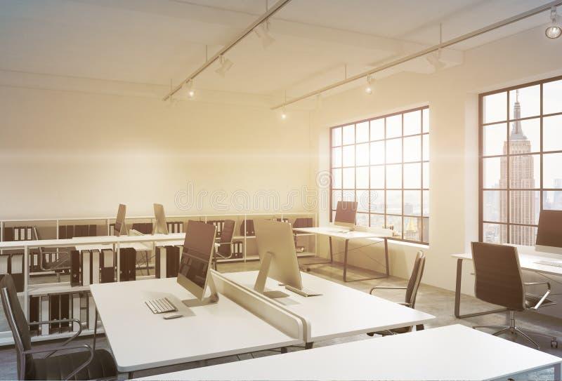 Posti di lavoro in un ufficio dello spazio aperto del sottotetto di tramonto Le Tabelle sono fornite di computer; scaffali di lib royalty illustrazione gratis