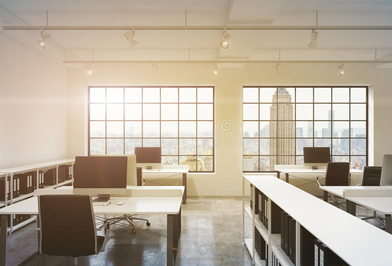 Posti di lavoro in un ufficio dello spazio aperto del sottotetto di tramonto Le Tabelle sono fornite di computer; scaffali di lib illustrazione di stock