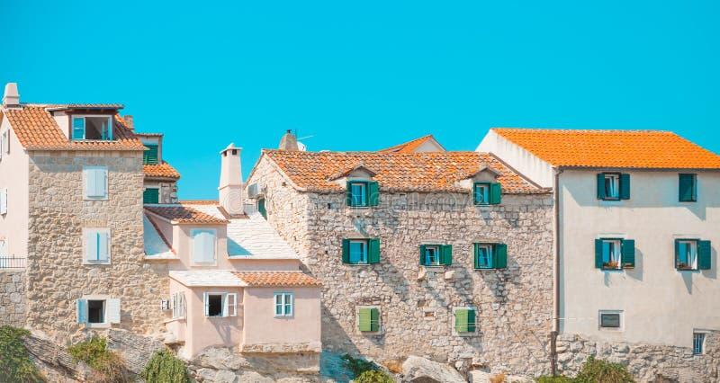 POSTIRA, CROAZIA - 18 LUGLIO 2017: Lotti di belle vecchie case costruite su roccia nel porto di una cittadina Postira - Croazia,  immagini stock