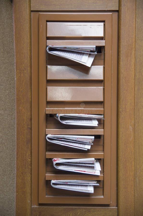 Postkästen gefüllt mit Werbungszeitungen stockbilder