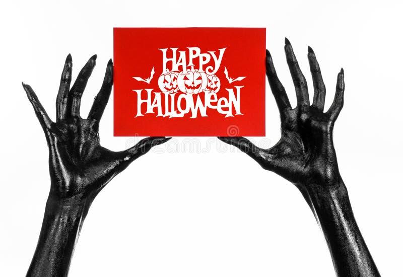 Postkarte und glückliches Halloween-Thema: die schwarze Hand des Todes eine Papierkarte mit den Wörtern glückliches Halloween hal stockfoto