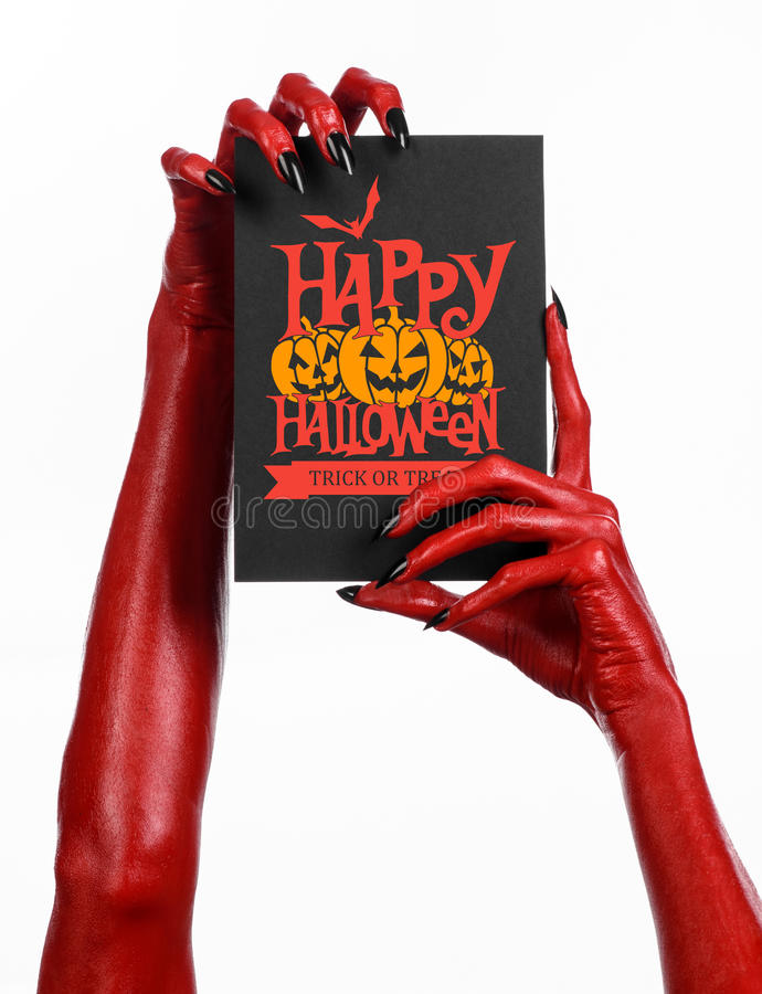 Postkarte und glückliches Halloween-Thema: Hand des roten Teufels mit den schwarzen Nägeln, die eine Papierkarte mit den Wörtern  stockbilder