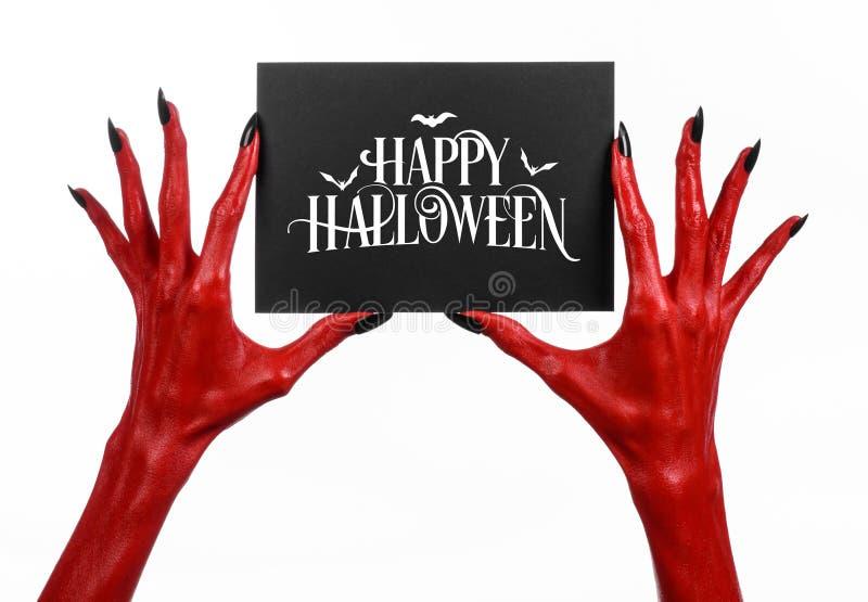 Postkarte und glückliches Halloween-Thema: Hand des roten Teufels mit den schwarzen Nägeln, die eine Papierkarte mit den Wörtern  stockfotografie