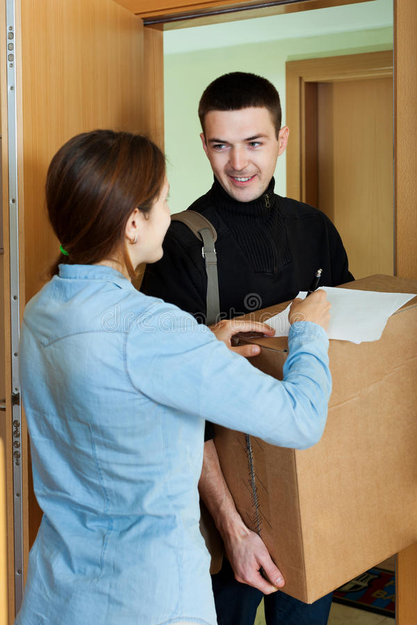 Postman brought package. Courier brought package to happy girl at home stock images