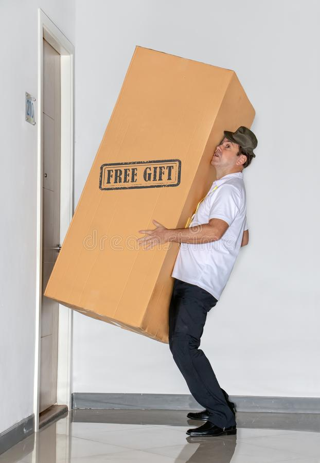 The postman carries a big package - free gift. The mail service carries a large shipment to the apartment stock photos
