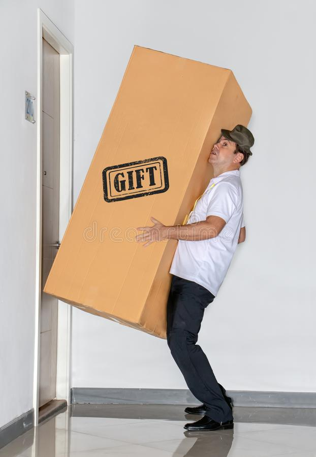 The postman carries a big package - gift. The mail service carries a large shipment to the apartment royalty free stock photos