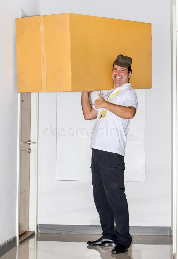 The postman carries a big package. On his shoulders. The mail service carries a large shipment to the apartment royalty free stock photography