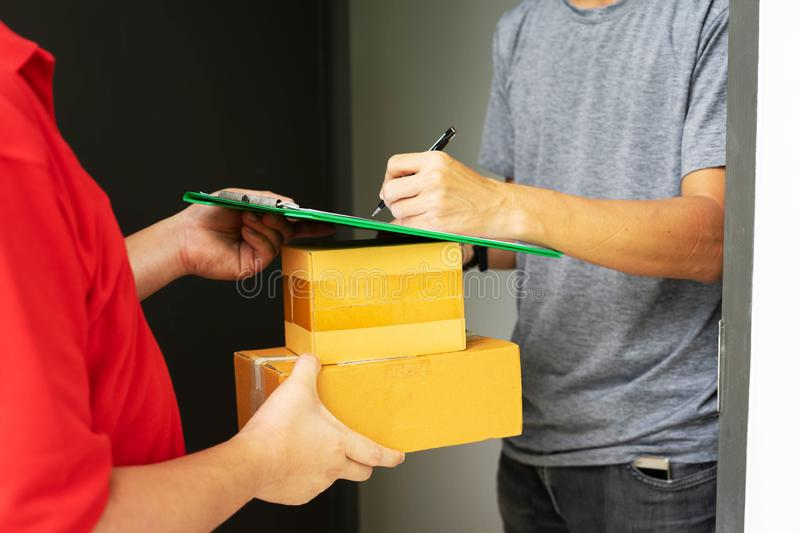 Postman delivering package of goods to home. Selective focus on the hands. Home delivery concept, Deliver packages to recipients stock photography