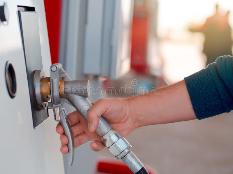 Posto de gasolina do veículo e a pessoa que guarda a bomba de gás imagens de stock royalty free