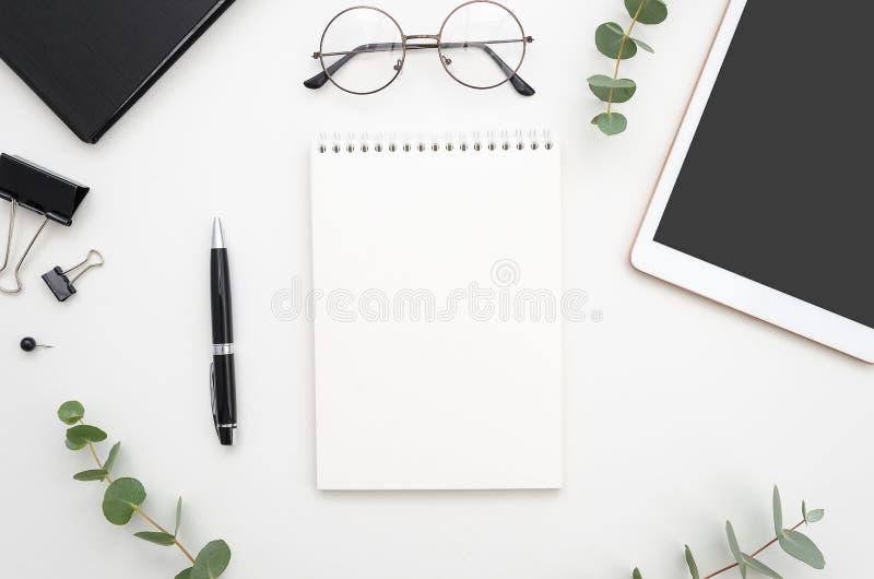 Posto di lavoro bianco dell'ufficio di vista superiore con il blocco note, la penna e la compressa a spirale con lo spazio della  fotografie stock libere da diritti