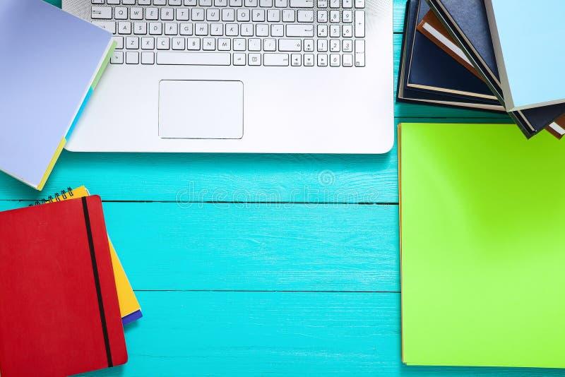 Posto di lavoro con i libri, la tastiera, i taccuini ed altri accessori su fondo di legno blu Spazio della copia e di vista super immagini stock