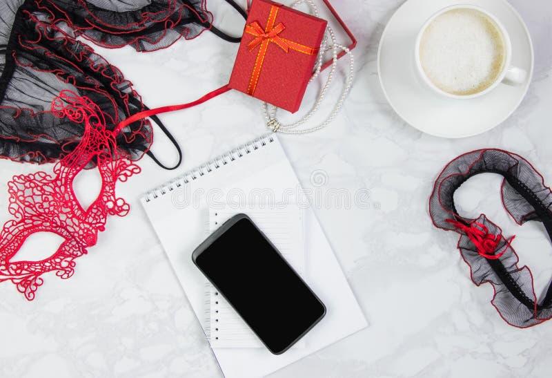 Posto di lavoro con il pizzo rosso e nero del blocco note, del telefono, giarrettiera per le calze, maschera del pizzo, contenito immagini stock libere da diritti