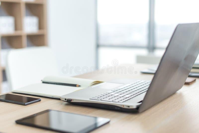 Posto di lavoro con la tavola di lavoro comoda del computer portatile del taccuino nella vista delle finestre e della città dell' immagini stock