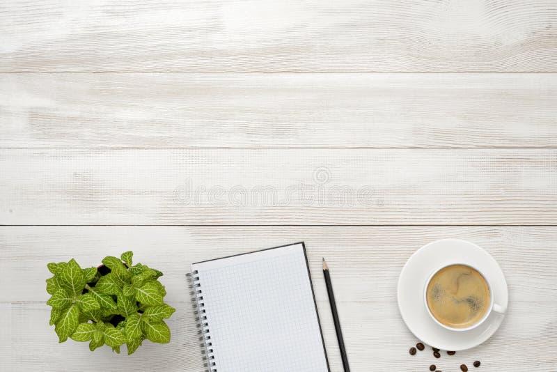 Posto di lavoro con la tazza di caffè, la pianta d'appartamento, il taccuino vuoto e la matita su superficie di legno nella vista fotografie stock
