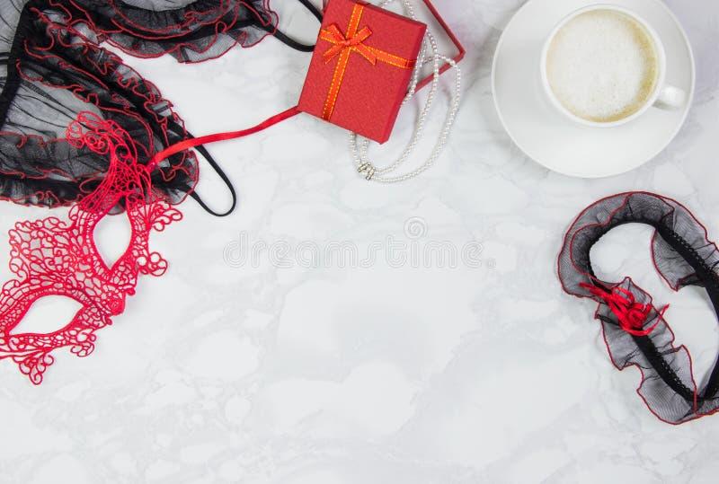 Posto di lavoro con pizzo rosso e nero, giarrettiera per le calze, maschera del pizzo, contenitore di regalo con una collana dell fotografia stock