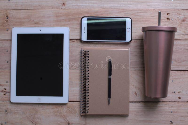 Posto di lavoro dell'ufficio Fondo di legno dello scrittorio con il computer portatile, il telefono cellulare, la tazza inossidab immagini stock