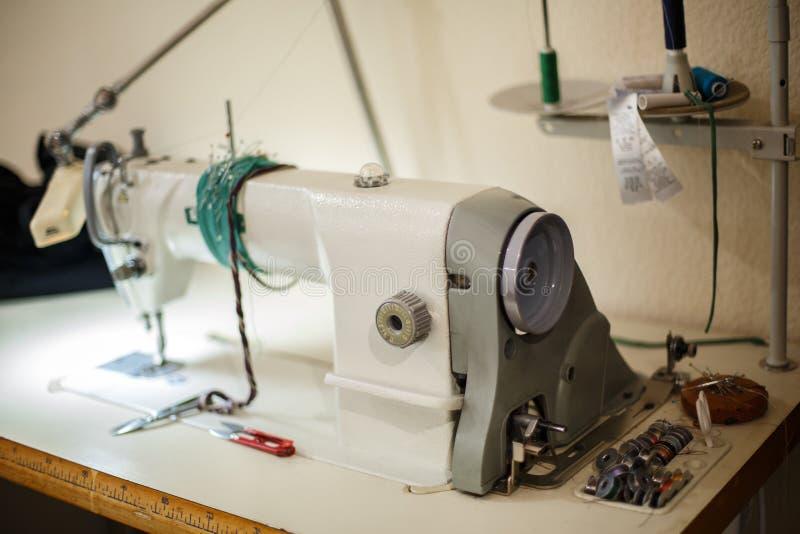 Posto di lavoro della cucitrice Fili di forbici della macchina per cucire ed altri strumenti Adattamento dell'industria fotografie stock