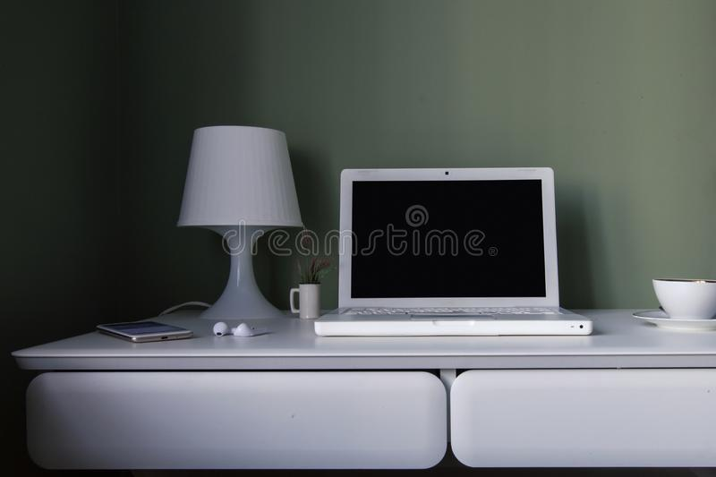 Posto di lavoro scandinavo di stile - tavola d'attaccatura bianca, computer portatile bianco e lampada di lettura fotografia stock