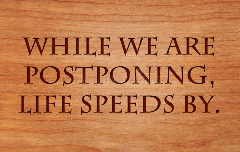 While we are postponing. Life speeds by - quote by Seneca on wooden red oak background royalty free stock image
