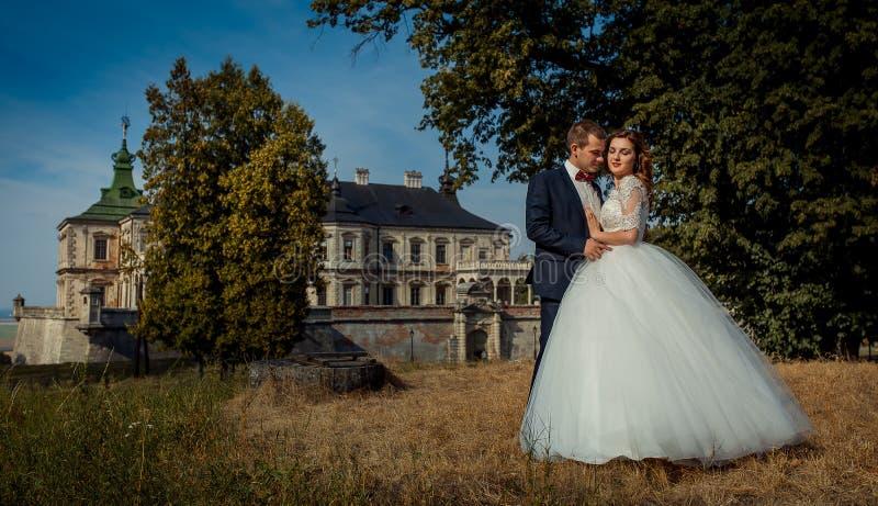 Postrait al aire libre romántico en el fondo del palacio viejo Pares de abrazo felices hermosos del recién casado foto de archivo libre de regalías