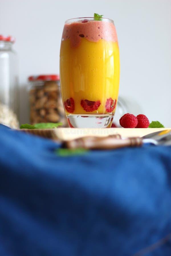 Postre acodado vegano fresco en un vidrio de smoothies coloreados del mango y del plátano con helado de las frambuesas imagen de archivo
