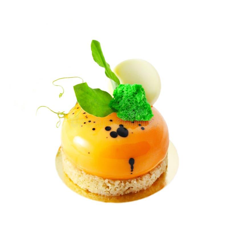 Postre anaranjado de la torta de zanahoria con las hojas verdes y el chocolate blanco fotografía de archivo
