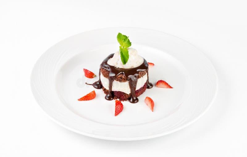 Postre con la torta de esponja del chocolate, la crema de la vainilla, la cereza, el helado y fresas en una placa en un fondo bla fotos de archivo libres de regalías
