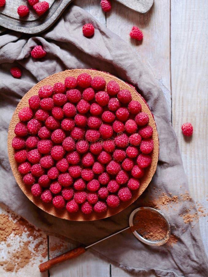 POSTRE CON LAS FRAMBUESAS Cierre del pastel de queso de la torta de chocolate para arriba, adornado con cacao y frambuesas Visión foto de archivo libre de regalías