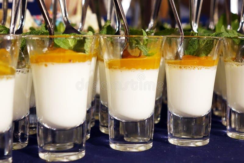 Postre cremoso y helado salado del caramelo en los tarros de cristal con la menta fresca fotos de archivo
