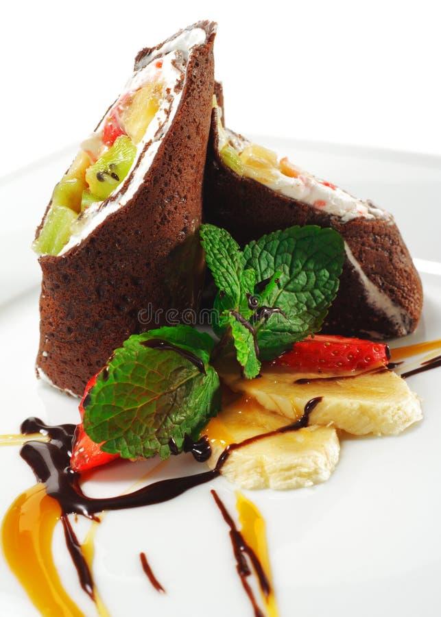 Postre - crepes del chocolate con las frutas foto de archivo