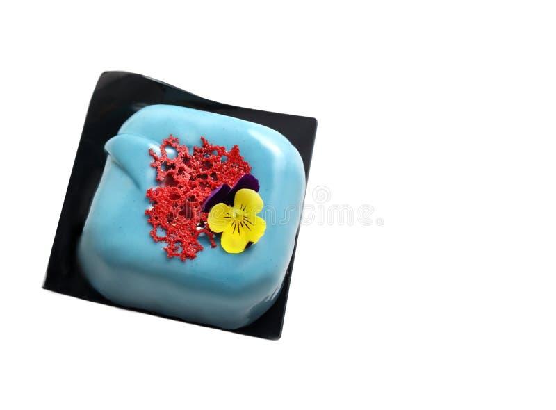 Postre cuadrado azul claro con crepé coralino rojo del cordón y flor comestible en blanco imágenes de archivo libres de regalías