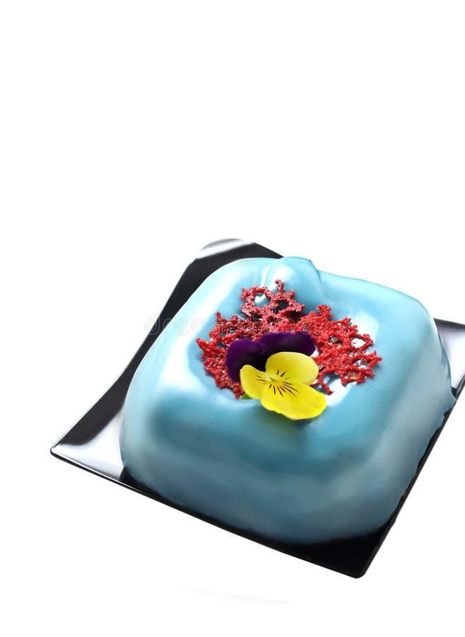 Postre cuadrado azul claro con crespón coralino rojo del cordón y la flor comestible del pensamiento fotografía de archivo