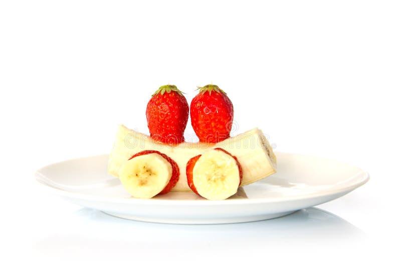 Postre de la diversión del plátano y de la fresa aislado en blanco imagen de archivo