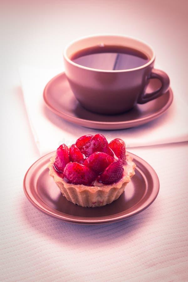 Postre de la fresa con la taza de té caliente fotografía de archivo libre de regalías