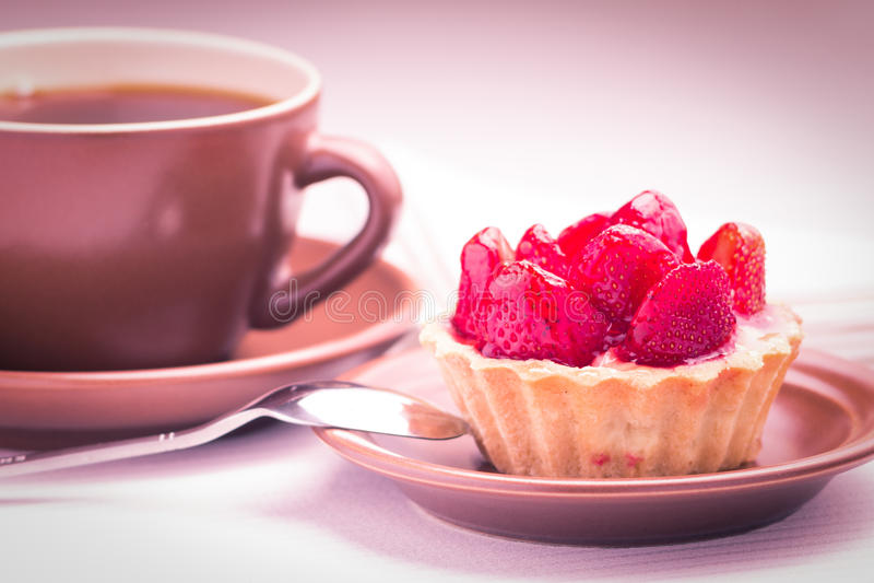 Postre de la fresa con la taza de té caliente fotos de archivo libres de regalías