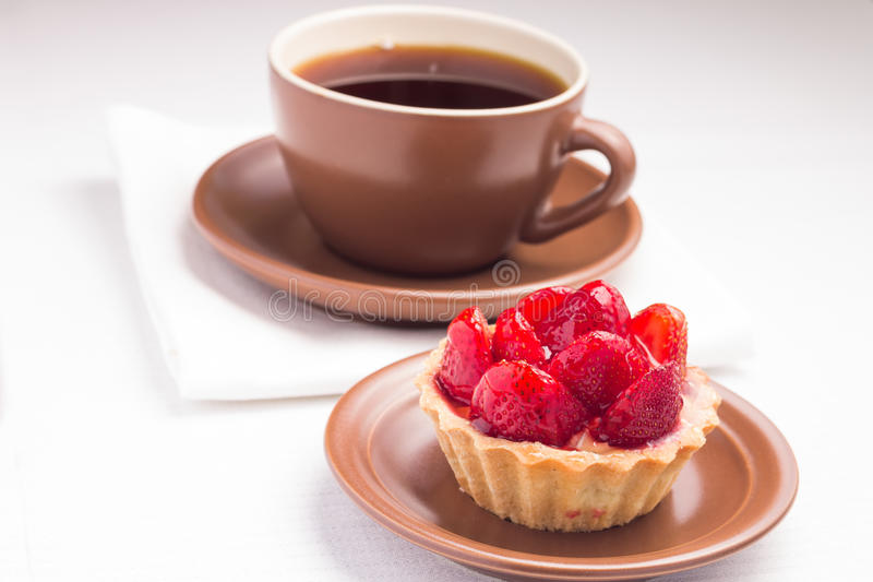 Postre de la fresa con la taza de té caliente imágenes de archivo libres de regalías