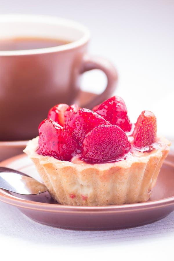 Postre de la fresa con la taza de té caliente imagen de archivo